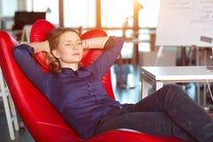 Entrepreneur féminin détendant dans la chaise rouge au bureau moderne Photographie stock