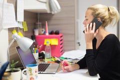 Entrepreneur féminin parlant au téléphone portable dans l'environnement de travail créatif moderne coloré Photos stock