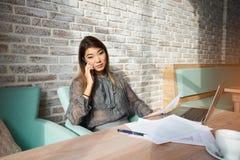 Entrepreneur féminin parlant au téléphone portable pendant le travail sur l'ordinateur portable c Images stock