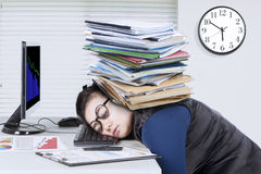 Entrepreneur feels tired with documents. Female entrepreneur feels tired with stack of document over her head while sleeps on desk Stock Photography
