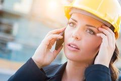 Entrepreneur femelle inquiété utilisant le casque antichoc sur le site utilisant la cellule pH image stock
