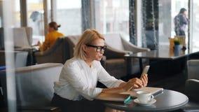 Entrepreneur gai de femme faisant l'appel visuel en ligne dans la main de ondulation parlante de café clips vidéos