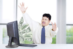 Entrepreneur get money from computer. Cheerful male worker celebrate his success while working in the office and get money from internet Royalty Free Stock Photo