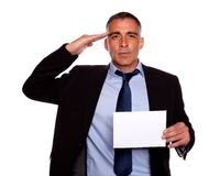 Entrepreneur greeting and holding a white card. Portrait of a entrepreneur giving a military salute and holding a white card with copyspace against white Royalty Free Stock Images
