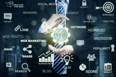 Entrepreneur hand holding SEO icon. Close up of a male entrepreneur hand protecting a SEO icon. Concept of Search Engine Optimization Royalty Free Stock Photo