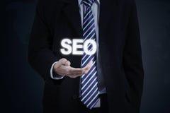 Entrepreneur hand holds SEO word Stock Images