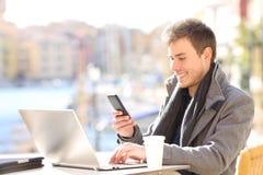 Entrepreneur heureux à l'aide du téléphone et de l'ordinateur portable dans une barre image stock