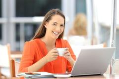 Entrepreneur heureux regardant l'appareil-photo dans une barre images stock