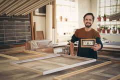 Entrepreneur holding up a framed bank note in his workshop Royalty Free Stock Photos