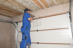 Entrepreneur installant l'ouvreur de porte de garage La porte de garage jaillit, remplacement de porte de garage, réparation de p photographie stock libre de droits