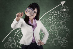 Entrepreneur with magnifier and business gear Stock Image