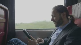 Entrepreneur man commuting on train relaxing his business trip watching through the window and browsing internet on tablet pc. Happy young entrepreneur man stock footage
