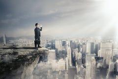Entrepreneur masculin criant sur la falaise photos stock