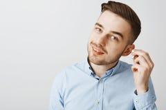 Entrepreneur masculin européen avec du charme dans la coupe de cheveux élégante enlevant l'earbud sans fil inclinant à l'ami de t images libres de droits