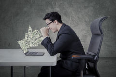 Entrepreneur with money from laptop Stock Photography