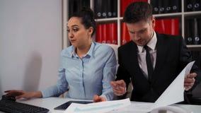 Entrepreneur montrant à son employé un document et répondant à l'appel banque de vidéos