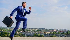 Entrepreneur in motion purposeful expression. Businessman formal suit carries briefcase sky background. Businessman royalty free stock image
