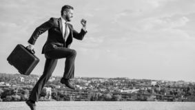 Entrepreneur in motion purposeful expression. Businessman formal suit carries briefcase sky background. Businessman stock photography