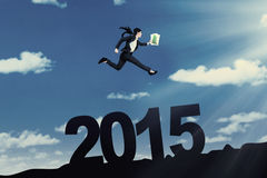 Entrepreneur with paperwork jumps over number 2015 Stock Images