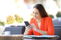 Entrepreneur s?rieux passant en revue le t?l?phone intelligent dans une terrasse de barre images libres de droits
