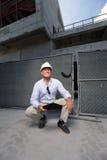 Entrepreneur s'accroupissant à un chantier de construction Photo stock