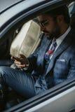 Entrepreneur s'asseyant dans la voiture et tenant ses lunettes de soleil images libres de droits