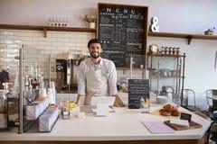 Entrepreneur se tenant derrière le compteur à un café images stock
