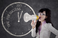 Entrepreneur shouting success in 2017 with megaphone. Image of a big clock showing text of time for success and numbers 2017 with beautiful woman shouted by Stock Photos