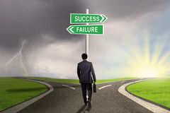Entrepreneur with signpost to success or failure. Male worker walking on the road and find two signpost with two choices to success or failure stock photo