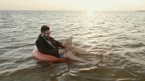Entrepreneur in the middle of the sea on a children`s inflatable circle working with a laptop. An entrepreneur sits in the middle of the sea at sunset and in a stock footage