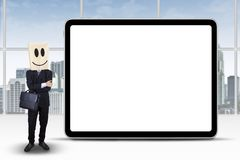 Entrepreneur with smiley face and empty board. Successful businessperson with a cardboard head standing next to empty billboard in the office Royalty Free Stock Images