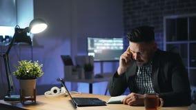 Entrepreneur soumis à une contrainte parlant au téléphone portable la nuit dans le bureau fonctionnant tard banque de vidéos