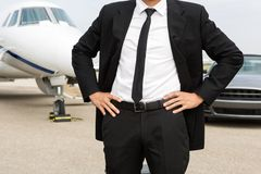 Entrepreneur Standing In Front Of Private Jet And. Midsection of entrepreneur with hands on waist standing in front of private jet and car Stock Photography