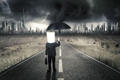 Entrepreneur standing on road with thunderstorm. Male entrepreneur with cardboard head standing on the road while carrying umbrella and briefcase with Stock Photo