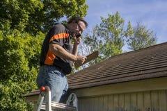 Entrepreneur sur l'échelle figure des dommages Reairs de grêle au toit Photo stock