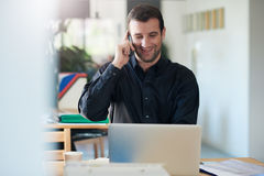 Entrepreneur talking business over the phone in an office Stock Photography