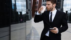 Entrepreneur talking on mobile cell phone in city. Urban male professional drinking coffee. Entrepreneur talking on mobile iphone in city business district stock video