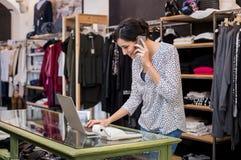 Entrepreneur talking at phone in shop Stock Images