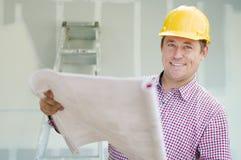 Entrepreneur tenant des modèles à l'intérieur du chantier de construction à la maison photos stock