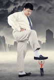 Entrepreneur try to trample his rival. Business competition concept with big businessman treading little entrepreneur Royalty Free Stock Photo