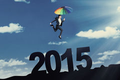 Entrepreneur with umbrella above number 2015 Stock Photos