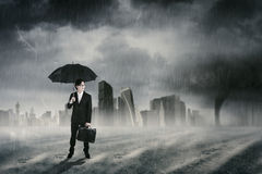 Entrepreneur with umbrella standing under rain Royalty Free Stock Photos