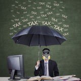 Entrepreneur with umbrella to protect from tax Stock Photography