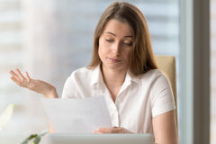 Entrepreneur upset because of low financial result. Businesswoman upset because of low financial results. Sad female entrepreneur reading document with bad Royalty Free Stock Photo