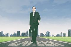 Entrepreneur walking above career word on the road. Portrait of American entrepreneur carrying a briefcase while walking above career word on the road Royalty Free Stock Photos