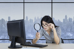 Entrepreneur watching computer with magnifier Stock Photos