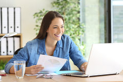 Entrepreneur working comparing documents online Stock Photography