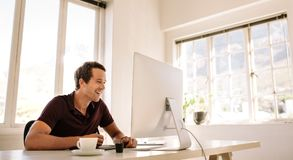Entrepreneur working on computer at home. Smiling businessman working on computer and using a digitizer to make notes. Man sitting at his work table working on Stock Photos