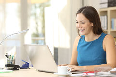 Entrepreneur working with a laptop at office. Happy casual entrepreneur working on line typing with a laptop at office with a window in the background Stock Photos