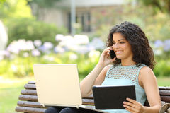 Entrepreneur working with multiple devices in a park. Entrepreneur working with multiple devices sitting in a bench in a park Stock Images